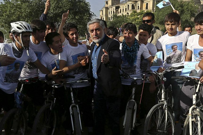 Afghan presidential candidate Abdullah Abdullah talks with a group of cyclists during the second round of the presidential candidate election campaign in Kabul on June 6, 2014.Two bombs exploded outside a hotel in western Kabul where presidential fro