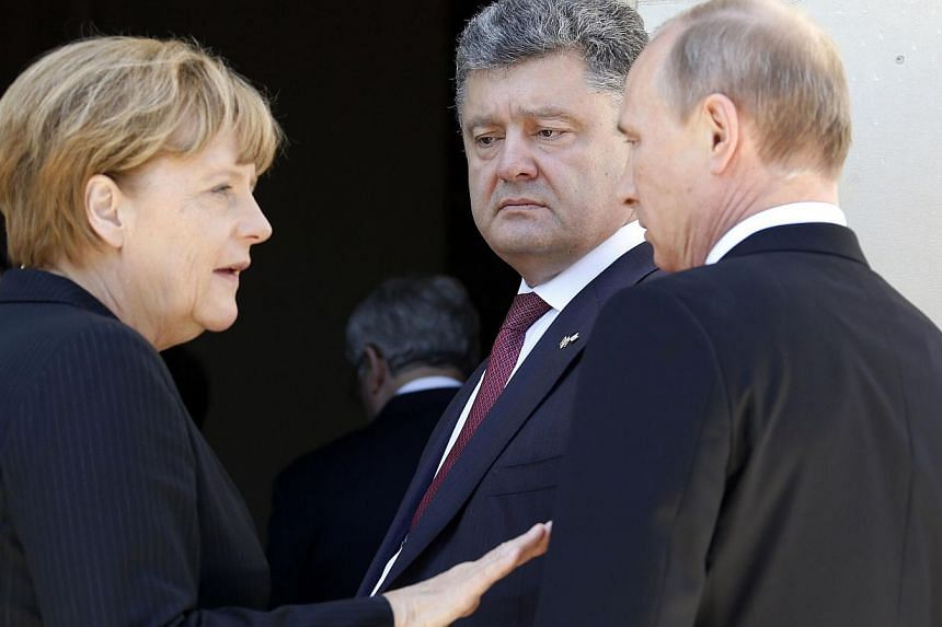 German Chancellor Angela Merkel (left), Ukrainian President-elect Petro Poroshenko and Russian President Vladimir Putin (right) speak following a group photo of world leaders attending the D-Day 70th Anniversary ceremonies at Chateau de Benouville in