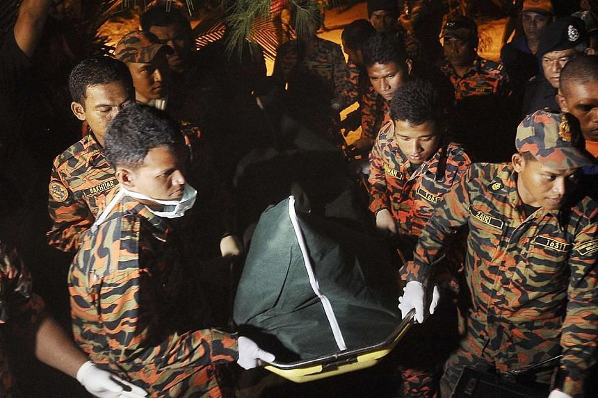 Search and rescue personnel carry a body during the search for missing British backpacker Gareth Huntley, 34, at Juara village on Tioman Island on June 4, 2014. -- PHOTO: REUTERS