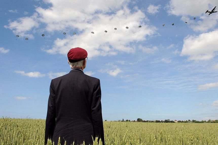 British World War II veteran Frederick Glover poses for a photograph as soldiers parachute down during a D-Day commemoration paratroopers launch event in Ranville, northern France, on June 5, 2014.World leaders and veterans paid tribute on the