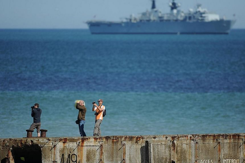 "People take pictures on a remain of the World War II ""Mulberry"" artificial harbour as a warship is anchored in the English Channel in Arromanches-les-Bains, Normandy, on June 6, 2014, during commemoration ceremonies marking the 70th anniversary of th"