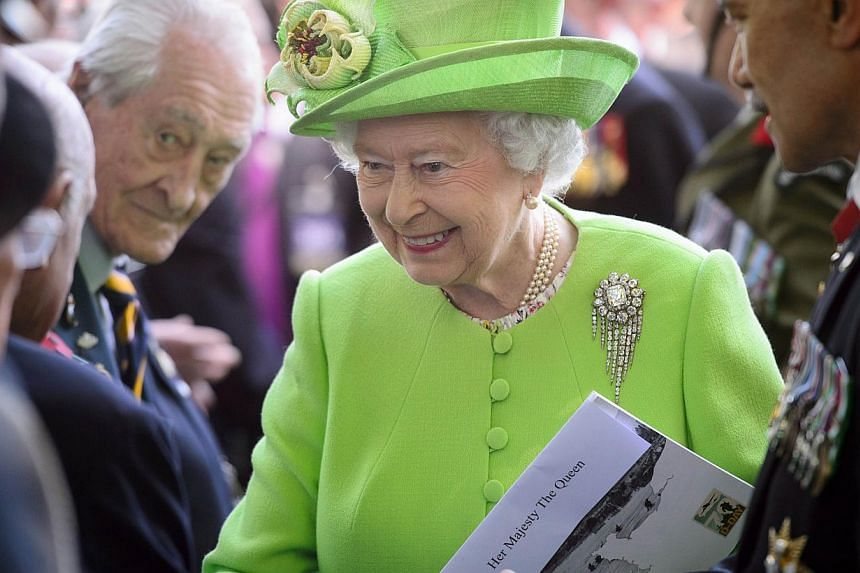 Britain's Queen Elizabeth II meets veterans following a British D-Day commemoration ceremony in Bayeux cemetery, northern France, on June 6, 2014, marking the 70th anniversary of the World War II Allied landings in Normandy. -- PHOTO: AFP