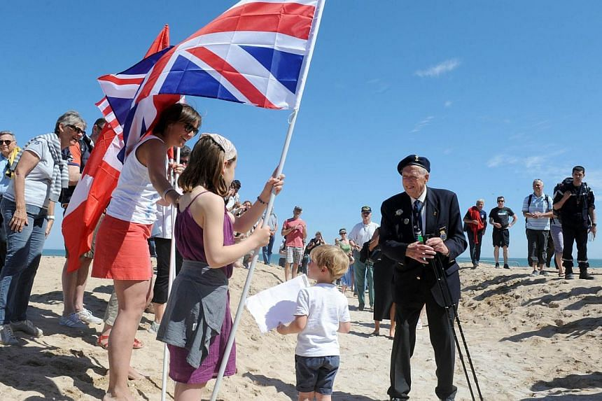 Norwegian World War II veterans are welcomed as they arrive for a joint French-Norwegian D-Day commemoration ceremony in Hermanville-sur-Mer, Normandy, on June 6, 2014, marking the 70th anniversary of the World War II Allied landings in Normandy.&nbs