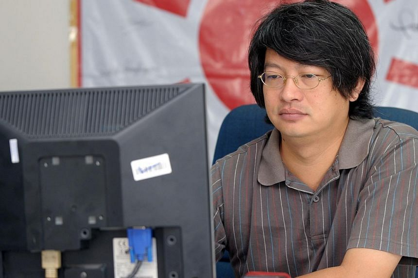 In a file picture taken on Oct 14, 2010, one of the new ''Red Shirt'' leaders, Sombat Boonngamanong, checks his page on the Facebook Internet social networking site at his office in Bangkok. Thailand's junta said on Friday that it had captured a
