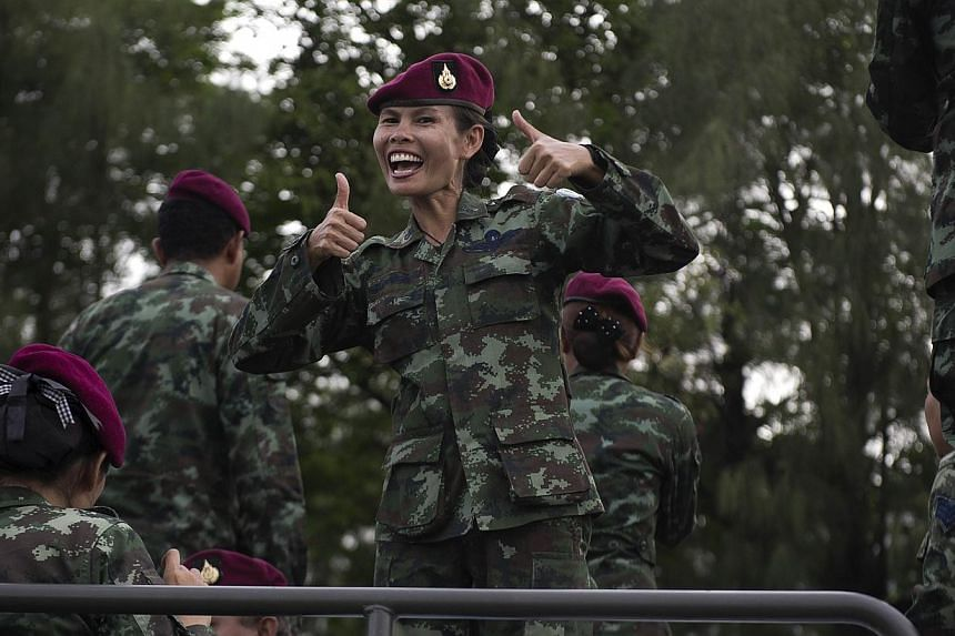 Thai soldiers sing as they stand on an army truck to entertain people at Victory monument in Bangkok on June 5, 2014. -- PHOTO: AFP