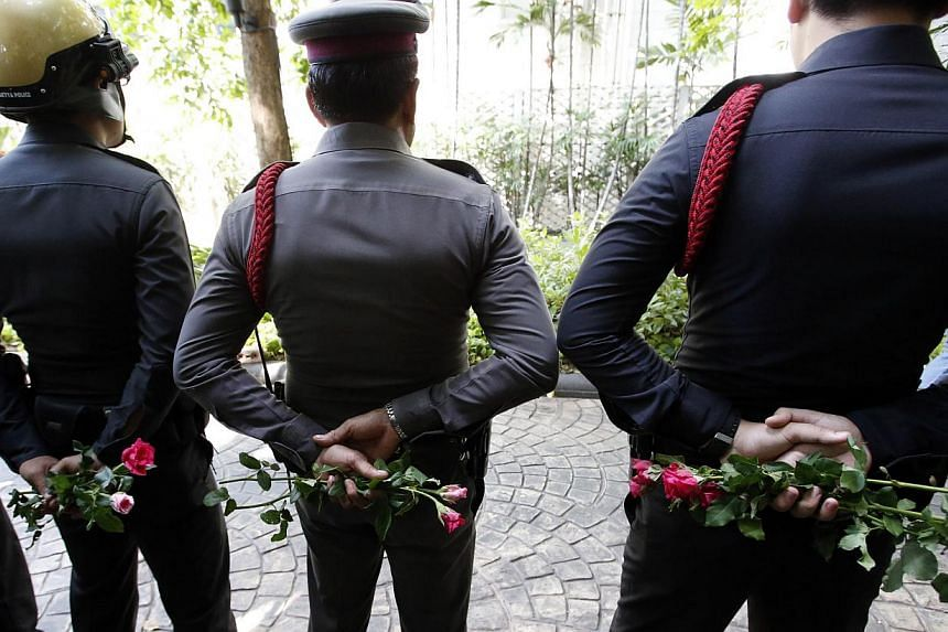 Thai policemen hold roses given by pro-army supporters behind their back as they stand guard outside the Australian embassy in Bangkok on June 4, 2014. -- PHOTO: REUTERS