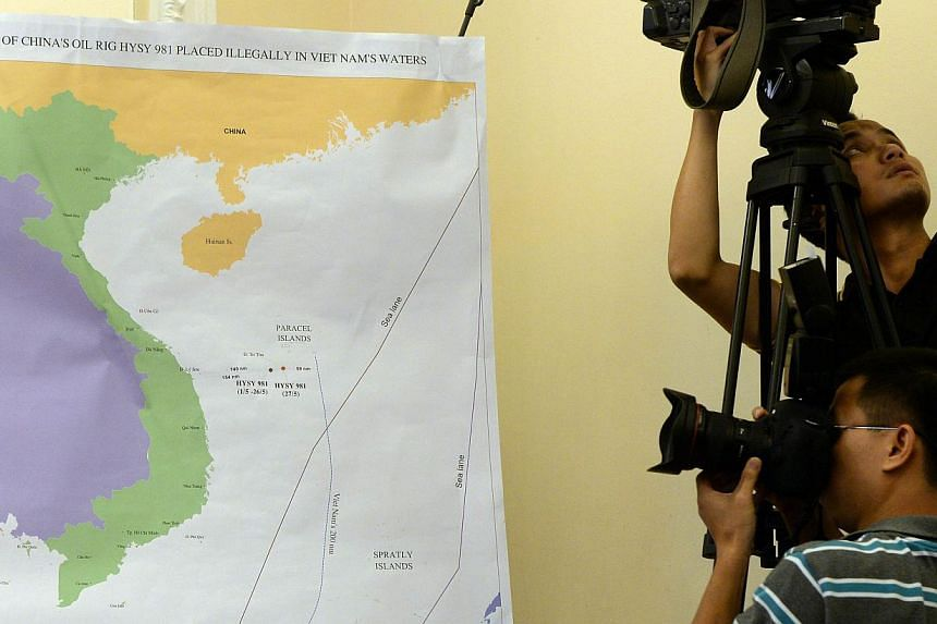 A photographer takes picture of a map showing the position of the Chinese oil rig in the disputed waters at the South China Sea during a press conference in Hanoi on June 5, 2014 held by Vietnamese Foreign Ministry accusing Chinese ships of attacking
