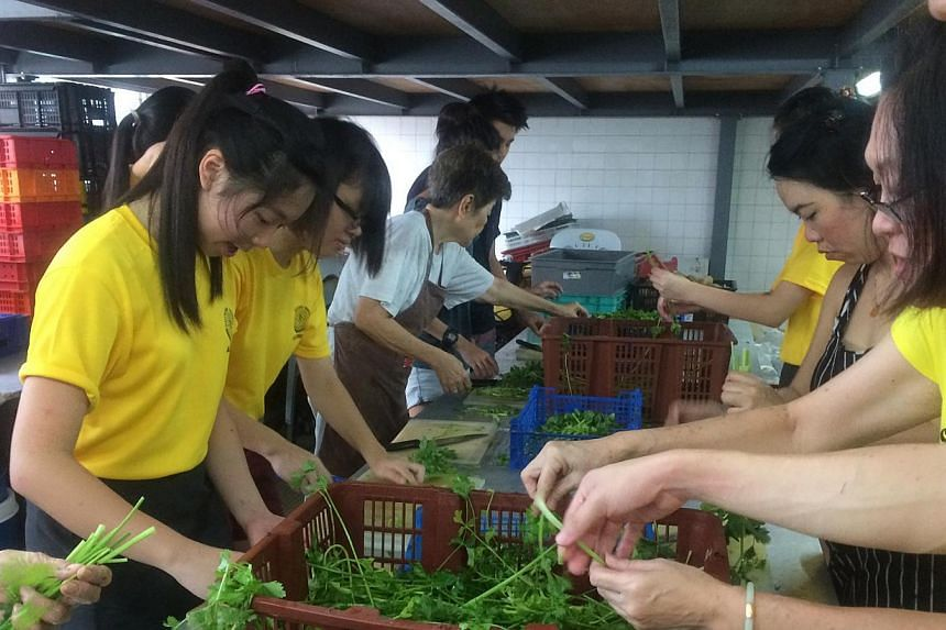 Pioneer Junior College student Lydia Phang (left) roped in 23 of her classmates to help prepare hot meals for the needy.