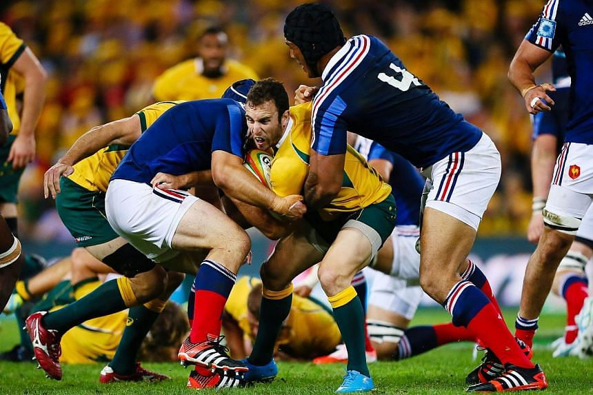 Australian halfback Nic White (centre) is tackled by France's Damien Chouly (left) during the first rugby union test match at Suncorp Stadium in Brisbane on June 7, 2014. -- PHOTO: AFP