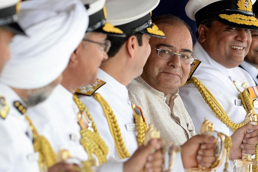India's new Finance Minister and Defence Minister Arun Jaitley (C) attends the commissioning ceremony of the two Indian Coast Guard ships 'Achook' and 'Agrim' at naval dockyard in Mumbai June 7, 2014. --PHOTO: REUTERS