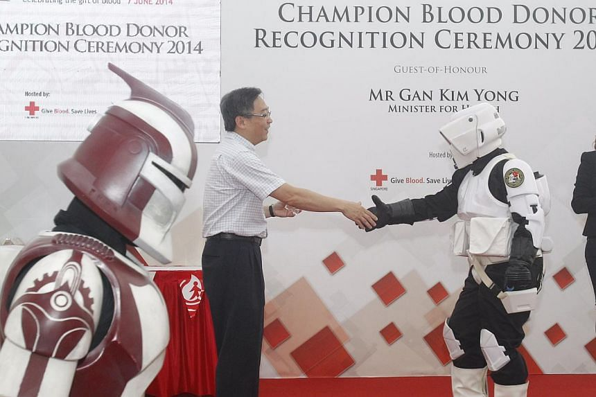 Ms Fatimah Ahmad Afandi (second from right), a 34-year-old exhibition guide, receives her gold award for blood donation from Health Minister Gan Kim Yong in her Storm Trooper costume during the Champion Blood Donor Recognition Ceremony on June 7, 201