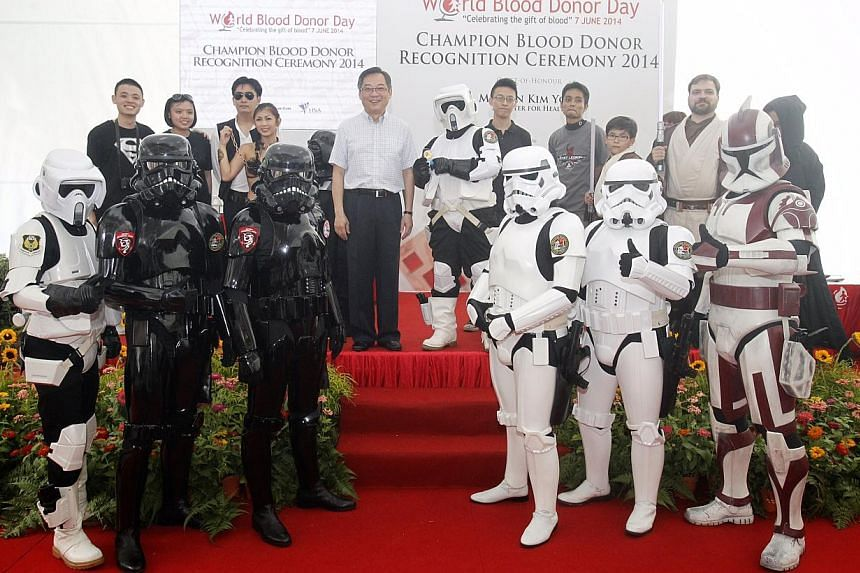 Ms Fatimah Ahmad Afandi (on minister's left), a 34-year-old exhibition guide, receives her gold award for blood donation from Health Minister Gan Kim Yong in her Storm Trooper costume during the Champion Blood Donor Recognition Ceremony on June 7, 20