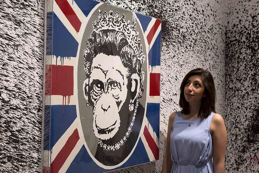 A gallery assistant poses with the work Monkey Queen at the Banksy: The Unauthorised Retrospective exhibition at Sotheby's S2 Gallery in London on June 6, 2014. -- PHOTO: REUTERS