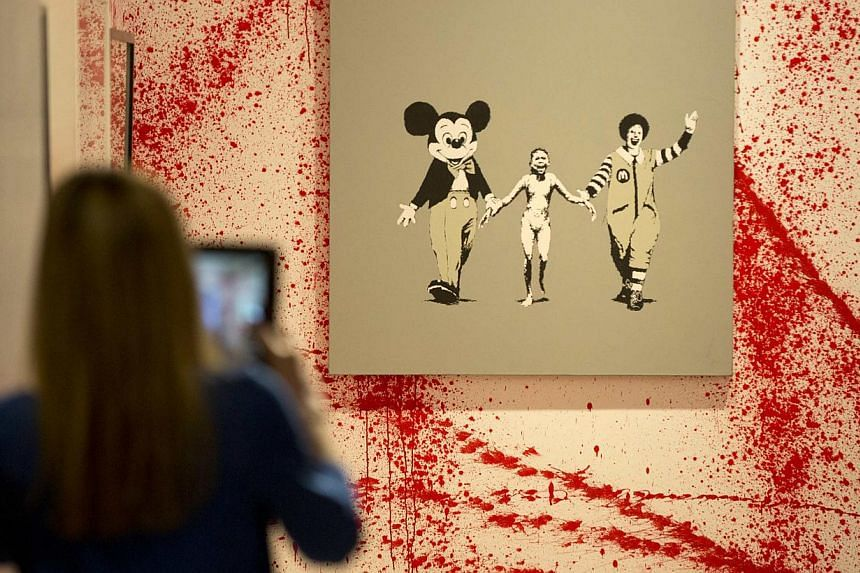 A woman photographs a work by the artist Banksy at the Banksy: The Unauthorised Retrospective exhibition at Sotheby's S2 Gallery in London on June 6, 2014. -- PHOTO: AFP