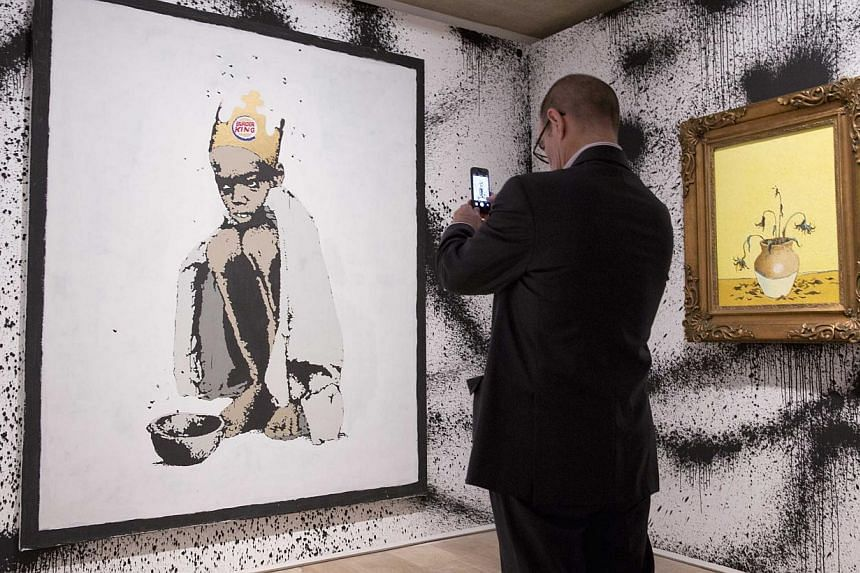 A man photographs the work Burger King at the Banksy:The Unauthorised Retrospective exhibition at Sotheby's S2 Gallery in London on June 6, 2014. -- PHOTO: REUTERS