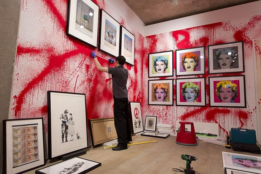 A Sotheby's employee hangs framed works of art in the first unauthorised retrospective of works by British graffiti artist Banksy in London on June 6, 2014. -- PHOTO: AFP