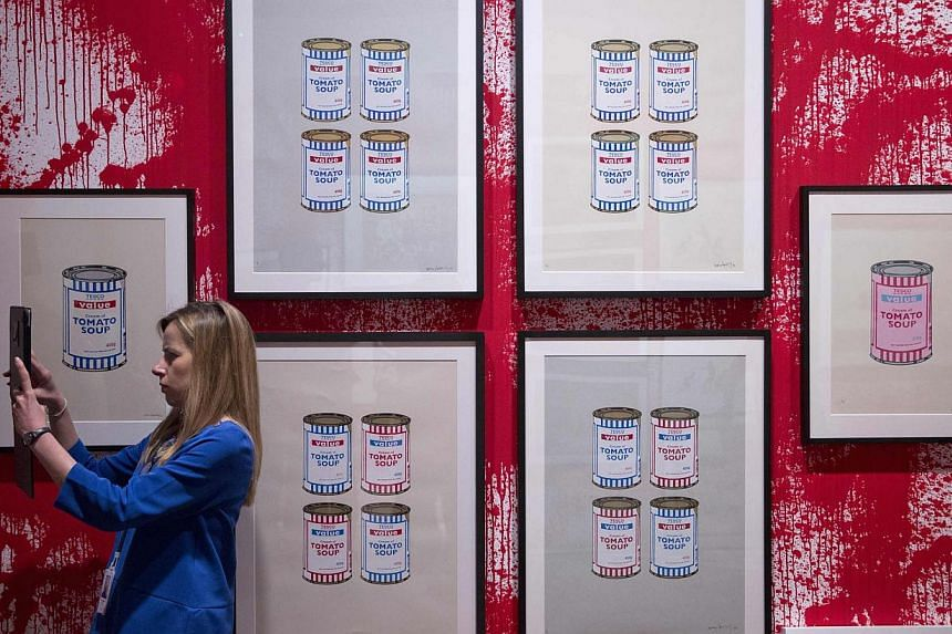 A woman takes a photograph at the Banksy: The Unauthorised Retrospective exhibition at Sotheby's S2 Gallery in London on June 6, 2014. -- PHOTO: REUTERS