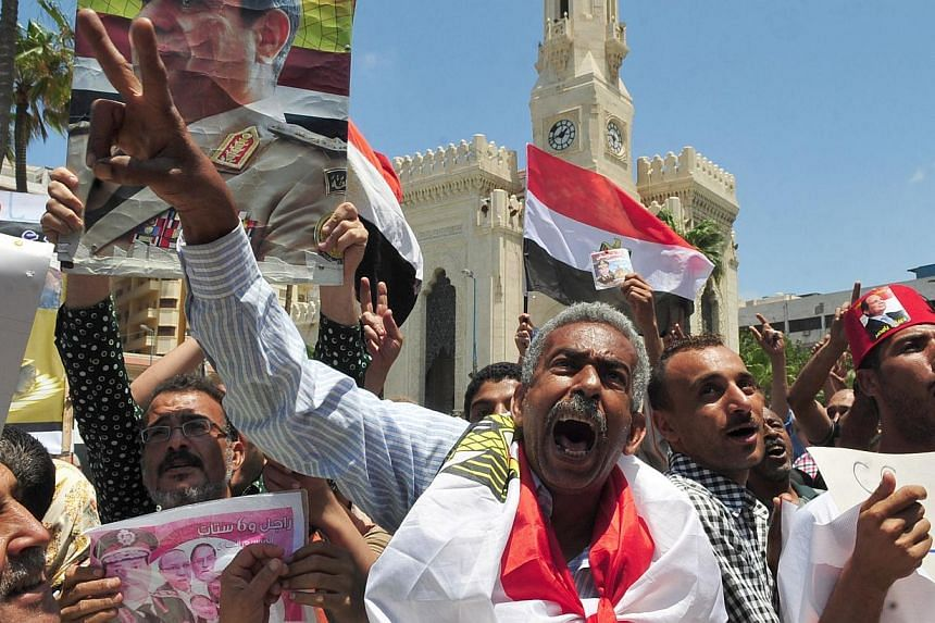 Egyptian protesters shout slogans and hold portraits of Egypt's new President Abdel Fattah al-Sisi on June 6, 2014, during a demonstration to show him their support, in the Mediterranean port city of Alexandria. -- PHOTO: AFP
