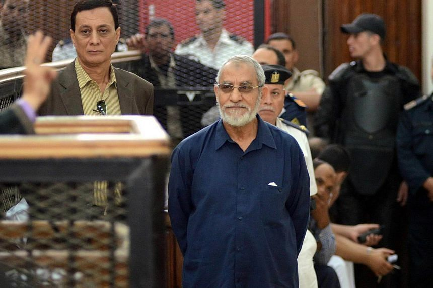 Egyptian Brotherhood's supreme guide Mohamed Badie (C) stands in front of his judges during his trial in the capital Cairo on May 18, 2014. An Egyptian court on Saturday postponed to July 5, the verdict in the trial of Muslim Brotherhood leader