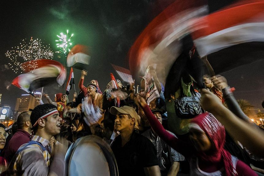 Egyptians celebrate in Cairo's landmark of Tahrir Square on June 3, 2014, after ex-army chief Abdel Fattah al-Sisi won 96.9 percent of the vote in Egypt's presidential election. -- PHOTO: AFP