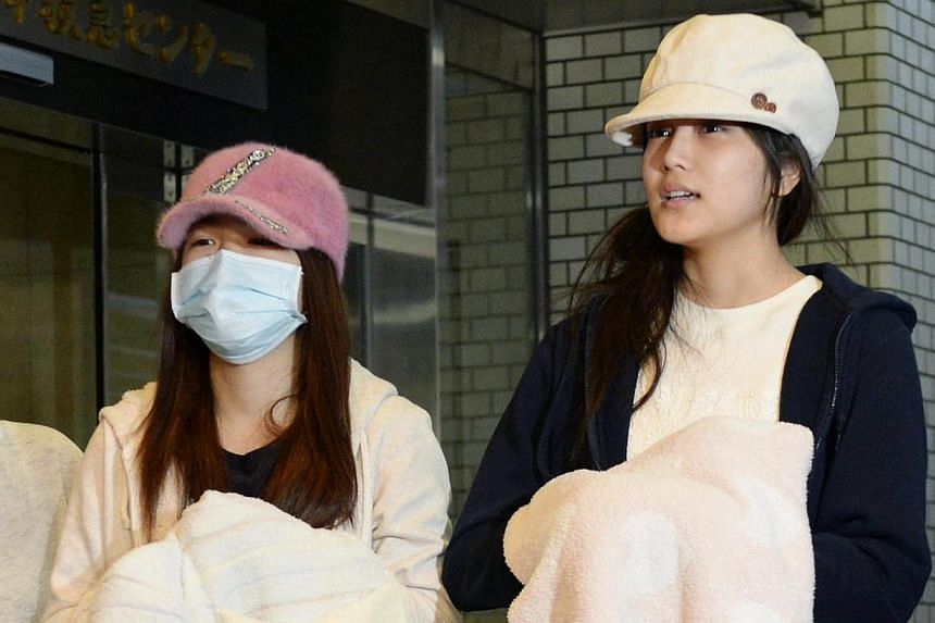 Members of Japanese female pop group AKB48 Rina Kawaei (left) and Anna Iriyama speak to the media as they are discharged from a hospital in Morioka, Iwate prefecture,in this photo taken by Kyodo May 26, 2014.-- PHOTO: REUTERS