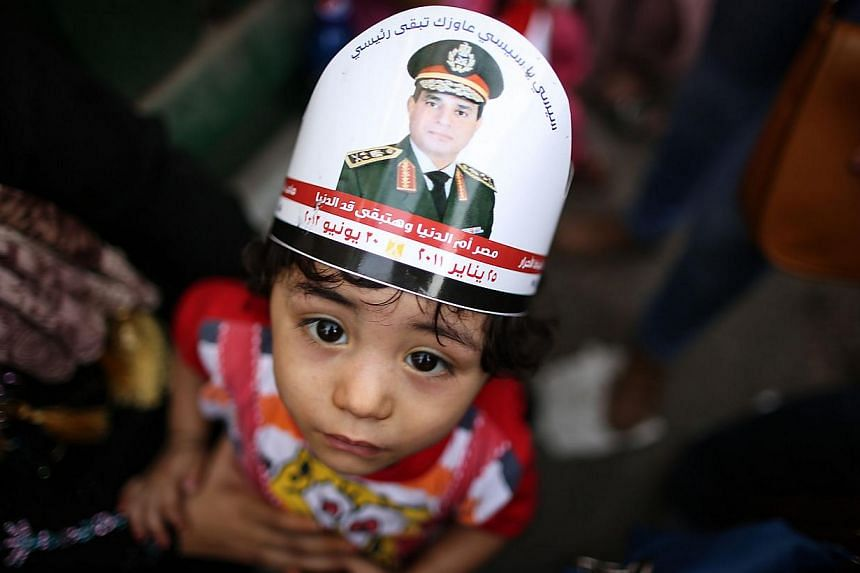 An Egyptian child with a portrait of ex-army chief Abdel Fattah al-Sisi on his head takes part in celebrations in Cairo's Tahrir Square on June 3, 2014, after Sisi won 96.9 percent of votes in the country's presidential election.-- PHOTO: AFP