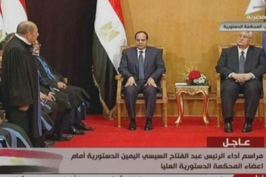 An image grab taken from Egyptian state TV shows ex-army chief and newly elected Egyptian President Abdel Fattah al-Sisi (center) sitting next to interim president Adly Mansour (right), during Sisi' swearing in ceremony, on June 7, 2014, in Cairo.&nb