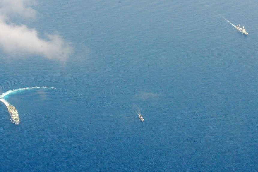 China Coast Guard ships (L and R) and a Philippine supply boat (C) engage in a stand off as the Philippine boat attempts to reach the Second Thomas Shoal, a remote South China Sea reef in the Spratly islands, claimed by both countries, on March 29, 2
