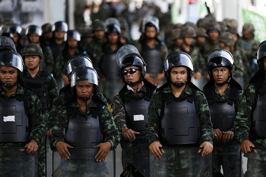 Soldiers block the entrance to an elevated train station near a shopping mall where anti-coup protesters gather in Bangkok June 1, 2014.Thailand's junta has prepared a force of over 6,000 troops and police for deployment in Bangkok on Sunday to
