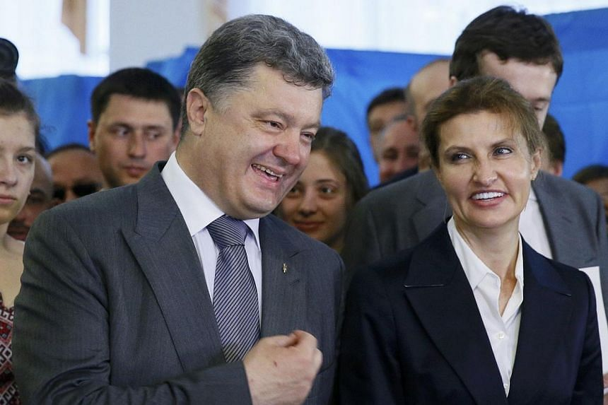 Ukrainian businessman, politician and presidential candidate Petro Poroshenko (left) and his wife Maryna (right), chat during voting in a presidential election at a polling station in Kiev May 25, 2014.With her natural elegance and confident ch