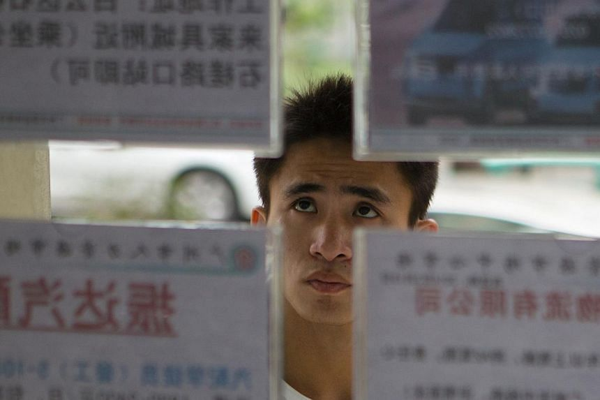 A job seeker looks at recruitment advertisements at a labour market in Guangzhou, Guangdong province on Feb 24, 2014. A record 7.27 million graduates - equivalent to the entire population of Hong Kong - will enter the job market this year; a market t
