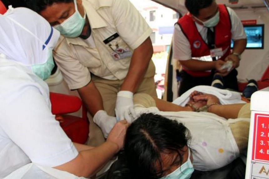 The maid being restrained before being taken to the Sibu Hospital. -- PHOTO: THE STAR/ASIA NEWS NETWORK