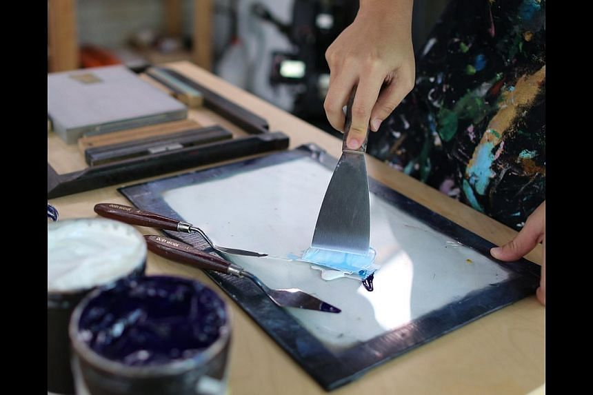 Printing a logo on a postcard. Step 1: Ms Goh mixes white and dark blue ink on a glass tile to produce a sky blue colour. -- ST PHOTO: ONG WEE JIN