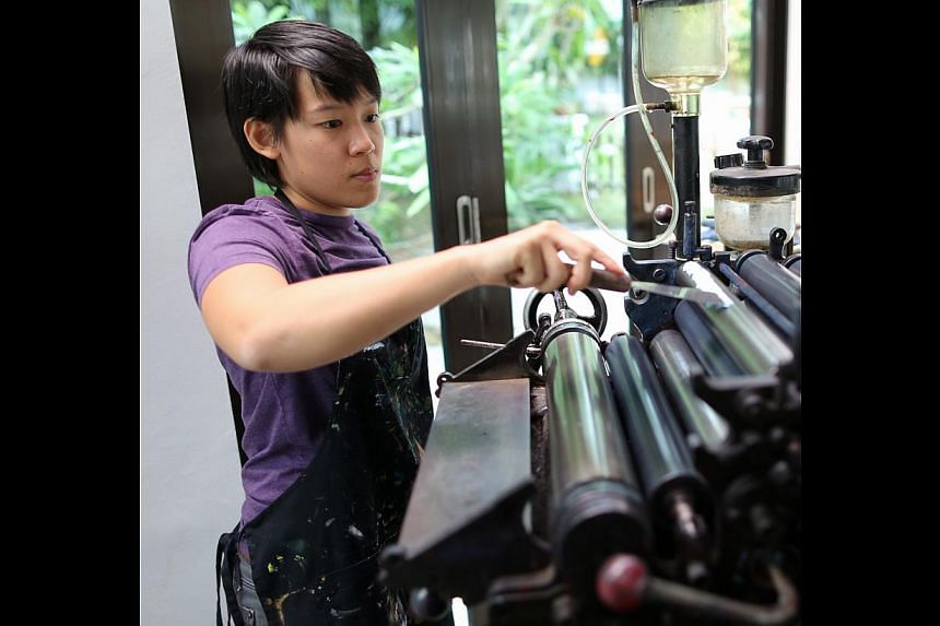 Printing a logo on a postcard. Step 2: She scrapes the blended ink off the tile and coats it on the ink machine roller on her Heidelberg press. Alever is pulled to spread the ink evenly on the roller. -- ST PHOTO: ONG WEE JIN