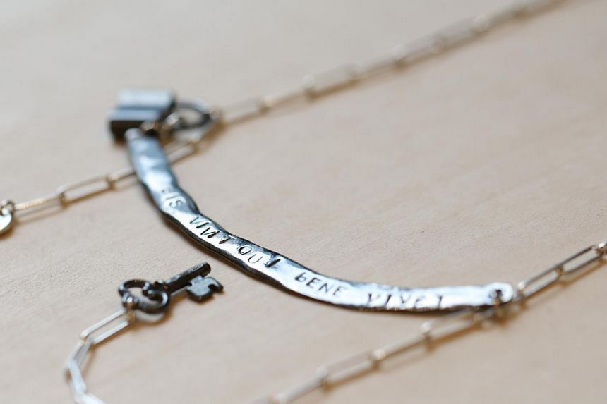 Long silver word necklace. -- ST PHOTO: ONG WEE JIN