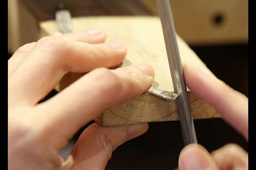 Making the long silver word necklace. Step 2: A file is used to smooth the rough edges of the cut silver and give the silver added depth and dimension. -- ST PHOTO: ONG WEE JIN