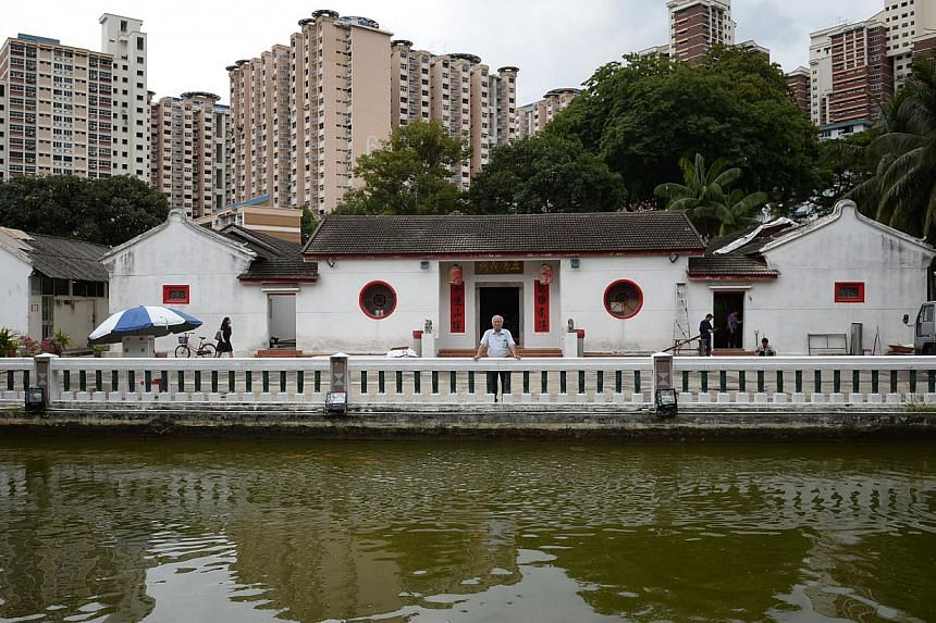 The Ying Fo Fui Kun memorial hall (left), seen in the distance from the cemetery in Commonwealth Lane. The mosaic-clad tombstones (right) stand in 65 uniform rows in the middle of a Housing Board estate. The Hakka clan association that owns the patch