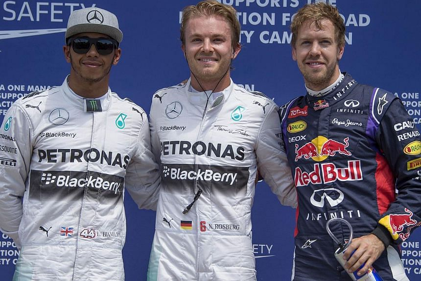 Pole position winner Mercedes driver Nico Rosberg (centre) of Germany stands with Mercedes driver Lewis Hamilton (left) of Britain and Red Bull driver Sebastian Vettel of Germany at the Circuit Gilles Villeneuve in Montreal on June 7, 2014 after the