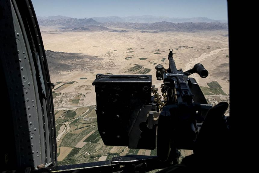 A file picture taken on June 2, 2014 shows a US Army helicopter gunner watching over the Afghan countryside while flying between Kandahar Airfield and Forward Operating Base Pasab in Kandahar. Afghanistan's air force is already woefully short of plan
