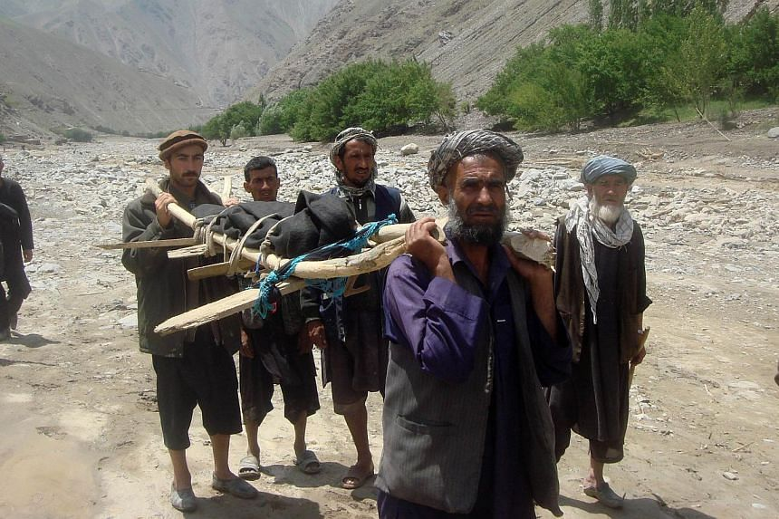 Afghan villagers transport the body of a victim after a flashflood landslide in the Guzargah-e-Nur district of Baghlan province on June 7, 2014. -- PHOTO: AFP