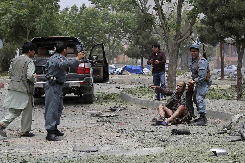 An Afghan policeman helps a wounded man after a suicide bomb attack in Kabul in this on June 6, 2014, picture provided by Abdullah Abdullah's campaign office.Security is being ramped up so the two candidates in Afghanistan's presidential electi