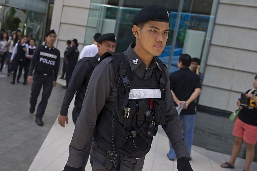 Thai policemen patrol prior to a demonstration by anti-coup protesters at a shopping mall in Bangkok on June 8, 2014.Thailand's junta kept many of the thousands of troops and police it readied to deal with protests in Bangkok on Sunday off the
