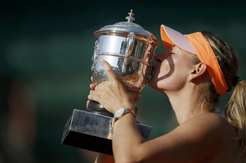 Maria Sharapova of Russia kisses the trophy as she poses during the ceremony after defeating Simona Halep of Romania during their women's singles final match to win the French Open tennis tournament at the Roland Garros stadium in Paris June 7, 2014.