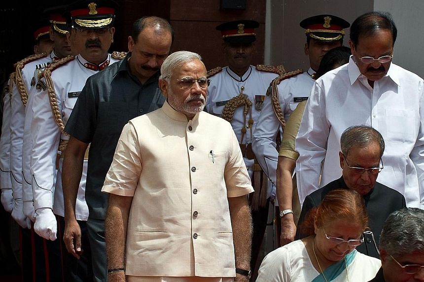 Indian President Pranab Mukherjee (2nd right, in black) arrives with Indian Prime Minster Narendra Modi (front left, in tan) to address the joint session of Parliament in New Delhi on June 9, 2014.India's new government pledged on Monday to mak