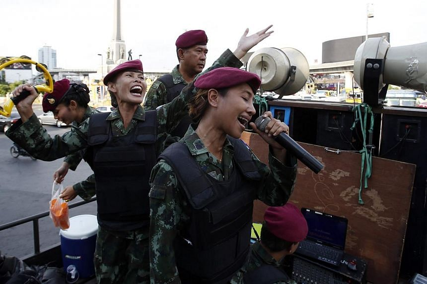 Female Thai soldiers sing patriotic songs on a military truck as soldiers and police take positions to prevent demonstrations against military rule at Victory Monument in Bangkok on June 3, 2014.A ballad penned by a coup-making army chief promi