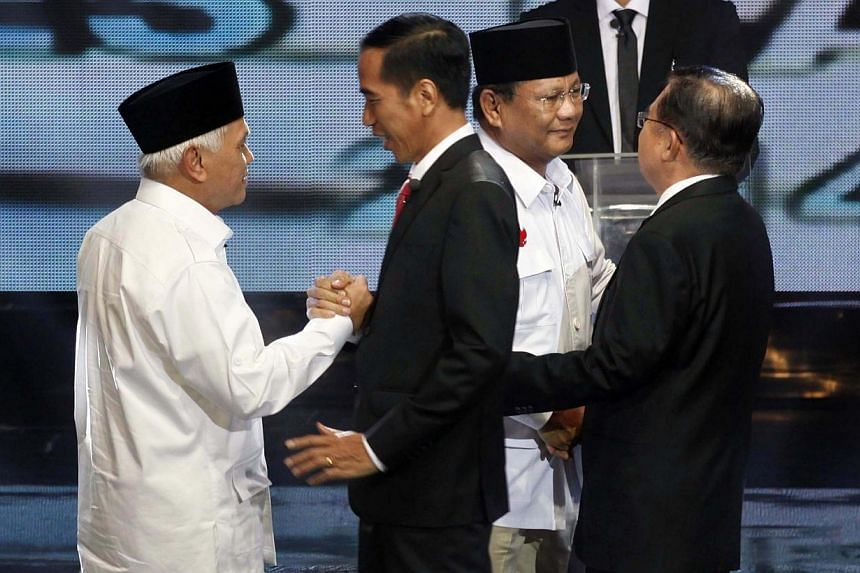 Indonesia's vice-presidential candidate Hatta Rajasa (left) greets presidential candidate Joko Widodo (second left), while presidential candidate Prabowo Subianto (second right) greets vice-presidential candidate Jusuf Kalla, before their presidentia