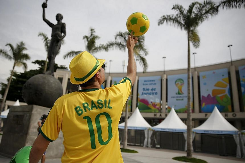 A street busker spinning a ball in Rio de Janeiro ahead of the World Cup. While the party is in full swing in Brazil, stockbrokers in Singapore are expecting commissions to drop by as much as 50 per cent during the World Cup period. -- PHOTO: REUTERS
