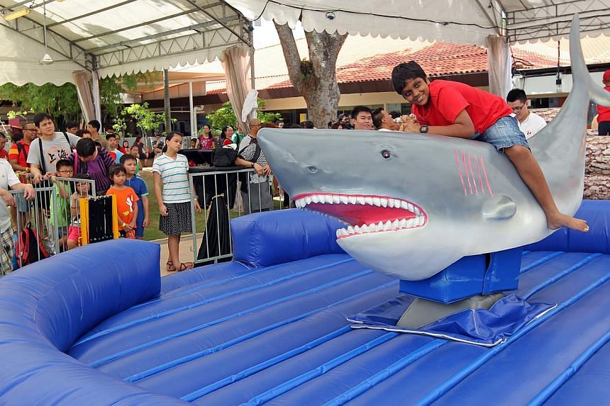 Maru Thuvel, 14, riding the rodeo shark at a carnival in Downtown East yesterday, the first of six fun fairs that NTUC will hold this year.
