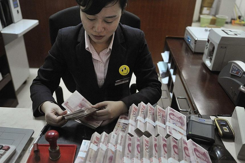A clerk counts 100 Chinese yuan banknotes at a branch of China Merchants Bank in Hefei, Anhui province, in this file photo. China's central bank announced details Monday of a plan that reduces the amount of money rural banks must keep in reserve, a m
