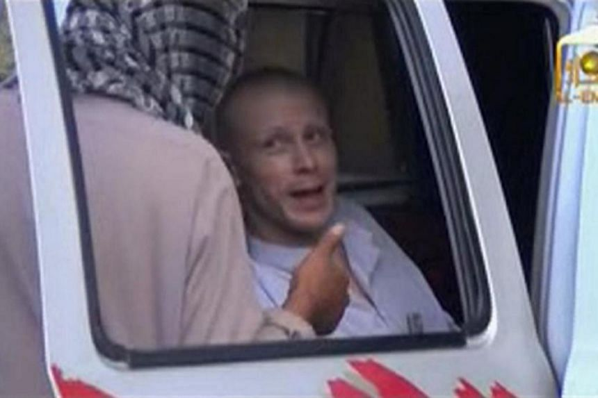 US Army Sergeant Bowe Bergdahl (right) talks to a Taliban militant as he waits in a pick-up truck before his release at the Afghan border, in this still image from video released on June 4, 2014. -- PHOTO: REUTERS